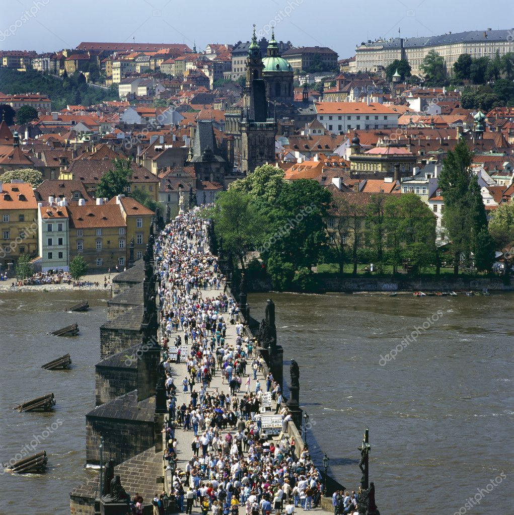 The Charles Bridge over the Vltava river,built in baroque style, in Prague is always crowded with tourists, artists and musicians. The part of the town on the o — Stock Photo #8288811