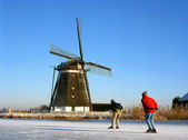 Windmill and skaters — Stock Photo
