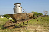 Wheelbarrow and milk churn — Stock Photo