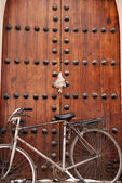 Bike parked against old door — Stock Photo