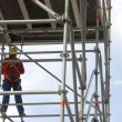 Foto Stock: Scaffold and worker