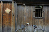 Bike against wooden house — Stock Photo