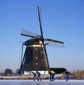 Windmill and skaters — Stockfoto