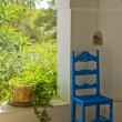 Antique Blue Wooden and Wicker Chair in a Porch and Sunlit Garden — Stock Photo #8467437