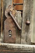 A very old door handle on a wooden door — Foto Stock