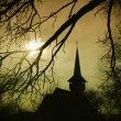 Church silhouette at sunset in Transylvania - Stock Photo