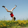 Young woman doing a cartwheel in a meadow — Stock Photo #8341717
