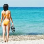 Woman in orange bikini holding flops on the shoreline — Stock Photo #8411726