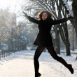 Young woman enjoying winter and jumping in the park — Stock Photo #8412988