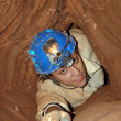 Narrow cave passage with a caver — Stock Photo