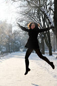 Young woman enjoying winter and jumping in the park — Zdjęcie stockowe