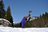 Young woman doing a cartwheel in the snow — Stock Photo