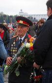 Un veterano caminando con flores, puede la celebración del día — Foto de Stock