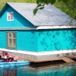 Stock Photo: Blue wooden boat house and white swnear lake