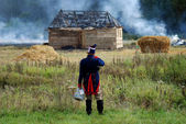 Man watching the house burning. Borodino battle historical reenactment. — Stock Photo