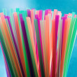 Many colorful cocktail straws on blue background — Stock Photo #9624184