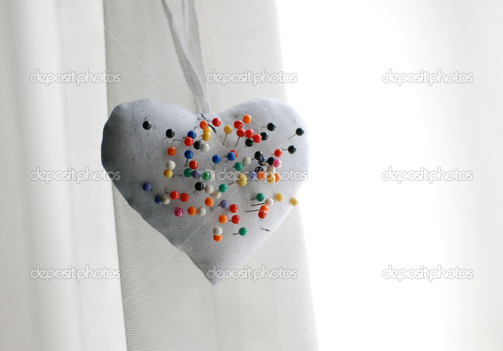 White heart-shaped pillow with many colorful pins on white background — Stock Photo #9623940