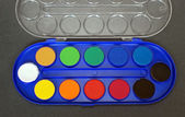 Colorful palette of watercolors on grey background — Stock Photo