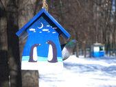 Pendaison de mangeoire oiseaux bleus d'un arbre et un pigeon à l'intérieur en hiver — Photo