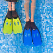 Underwater kids legs in fins in swimming pool — Stock Photo