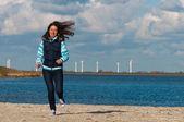 Happy active woman runs on beach — Stock Photo