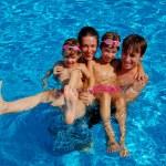 Счастливая семья из четырех веселятся в бассейне — Стоковое фото