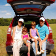 Happy smiling family of four near their car on vacation trip - Stock Photo