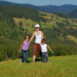 Active mother and children on their vacation in mountains — Stockfoto