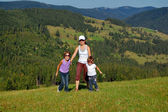 Active mother and children on their vacation in mountains — Stock Photo