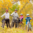 Stock Photo: Happy active family cycling on bikes outdoors