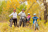 Happy active family cycling on bikes outdoors — Stock Photo