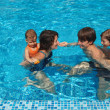 Happy active family with kids in swimming pool — Stock Photo #8974246
