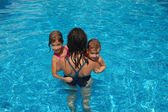 Happy active mother with kids in swimming pool — Stock Photo