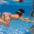 Active underwater family in swimming pool — Stock Photo #9184269
