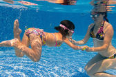 Active underwater family in swimming pool — Stock Photo