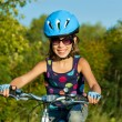 Happy girl cycling outdoors - Photo