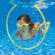 Happy child swims underwater in swimming pool — Stock Photo