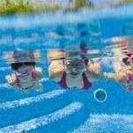 sott'acqua sorridente famiglia divertendosi e giocando in piscina — Foto Stock
