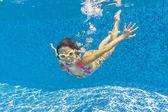 Happy child swims underwater in swimming pool — Stock Photo