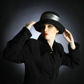 Fashion portrait of woman in black hat and coat — Stock Photo