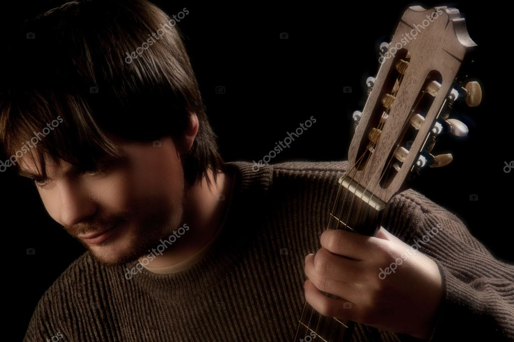 Guitar fingerboard and guitarist. Artistic portrait of man with hand on fingerboard. Black background — Stock Photo #8608560