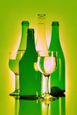 Bottle and wineglass with beverage. Green still-life — Stock Photo