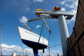 Sailboat lift up by a boat lifter — Stock Photo
