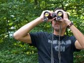 Young man looking through binoculars — Stock Photo