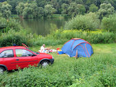 Camping tent by a river — Stock Photo