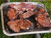 Juicy steaks in camping BBQ — Stock Photo