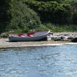 Small fishing boat dory rowboat on the shore — Stock Photo