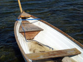 Small fishing boat dory rowboat on water — Stock Photo