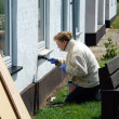 Woman with a paintbrush painting a house — Stock Photo