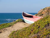 Beach landscape - Skiff boat on the cliff — Stock Photo